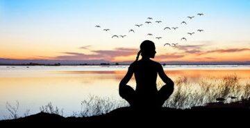 femme détendue assise avec coucher de soleil